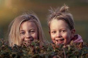 bambini felici dietro un cespuglio