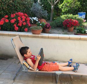 Giuliano sulla sdraio con il suo tablet in giardino