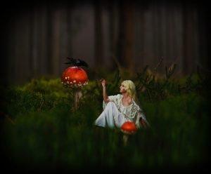 donna vestita di bianco seduta tra l'erba in un bosco, si sporge verso un corvo nero che sta su uno dei due funghi rossi giganti