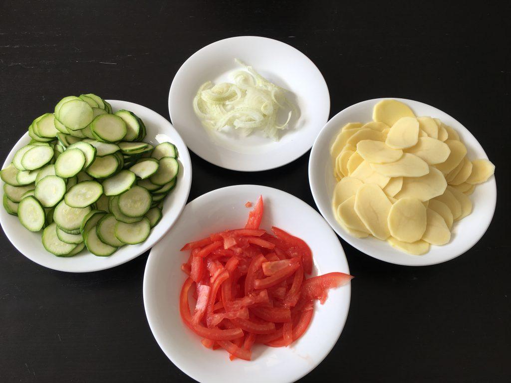 pomodori, zucchine, cipolla e patate fatte a fettine sottili in quattro piatti distinti