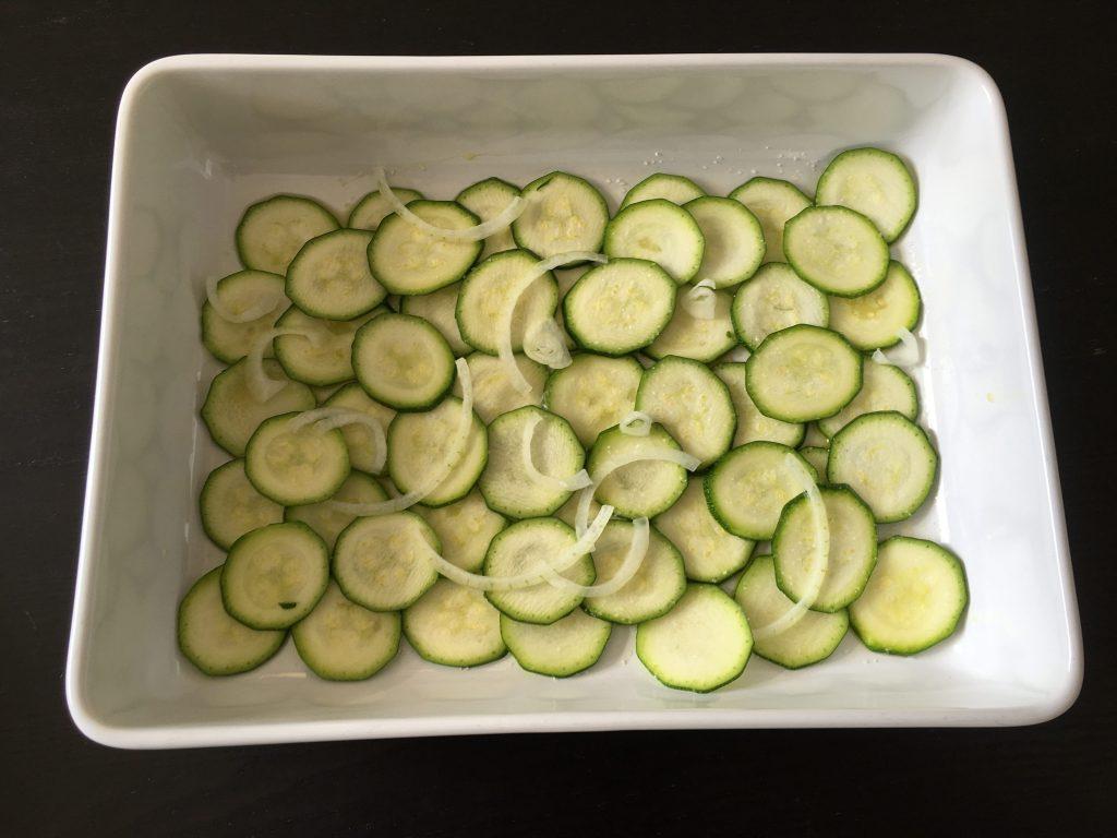 strato di zucchine a fette con cipolle su teglia da forno