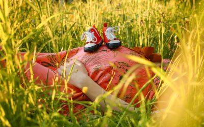 una donna incinta sdraiata su un prato della quale si vede solo il pancione sopra il quale ha appoggiato due scarpine da tennis rosse