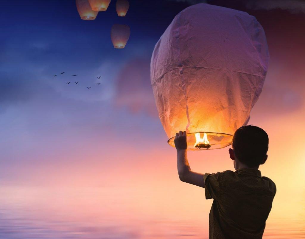 un bambino di spalle che al tramonto fa volare una lanterna in cielo