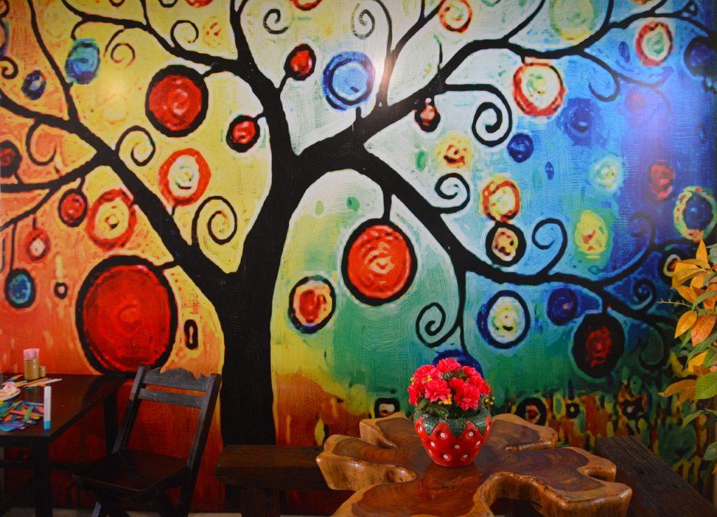 un ambiente scolastico per bambini con albero disegnato alla parete,tavolo fatto a tronco d'albero,vaso di fiori a forma di fragola e matite colorate su un altro tavolino