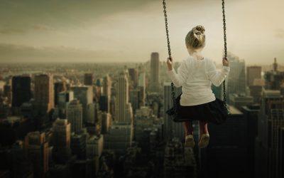 una bambina di spalle su un'altalena sopra newyork