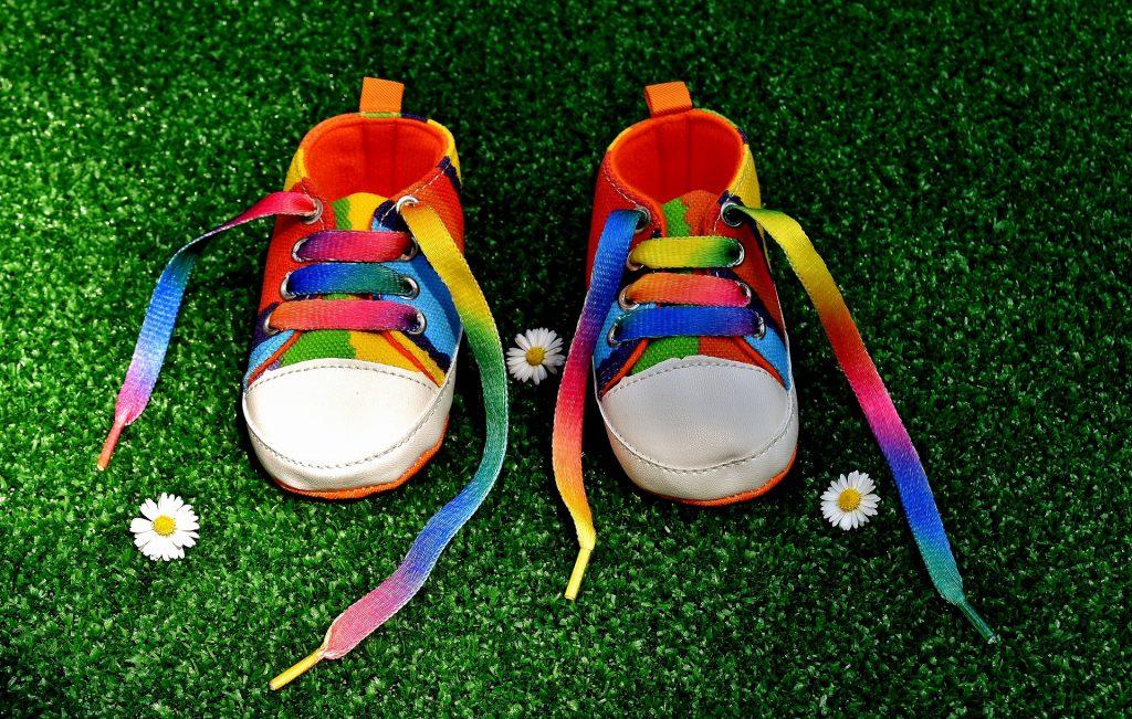 scarpe da tennis di un bambino piccolo dei colori del'arcobaleno