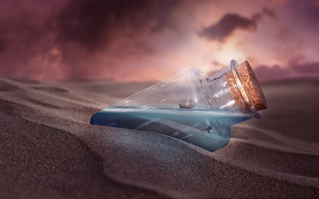 in mezzo al deserto una bottiglia con acqua, un pesce e una piccola barca dentro