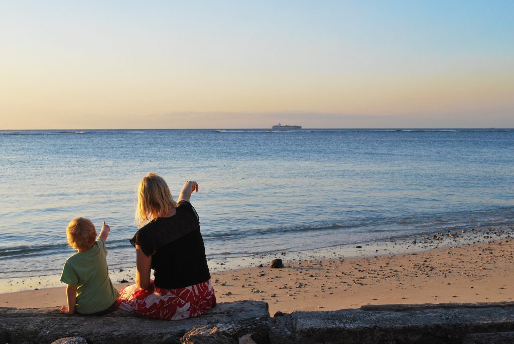 madre e figlio seduti di spalle indicando qualcosa all'orizzonte verso il mare