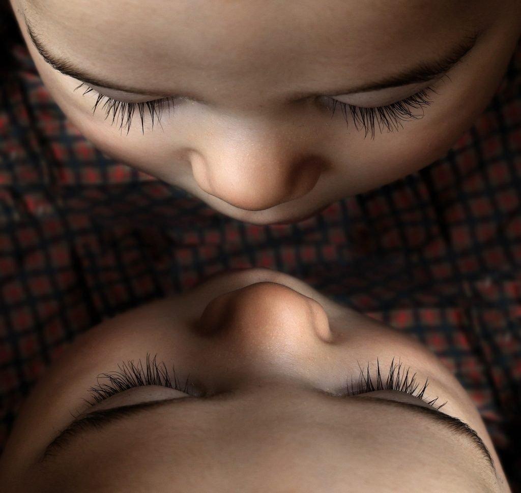 viso di un bambino visto dall'altro ed il suo riflesso nello specchio