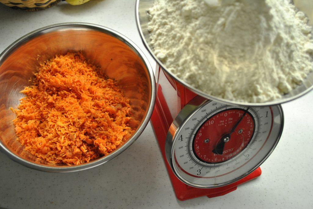 ciotola in metallo con carote grattugiate accanto a una bilancia che sta pesando la farina