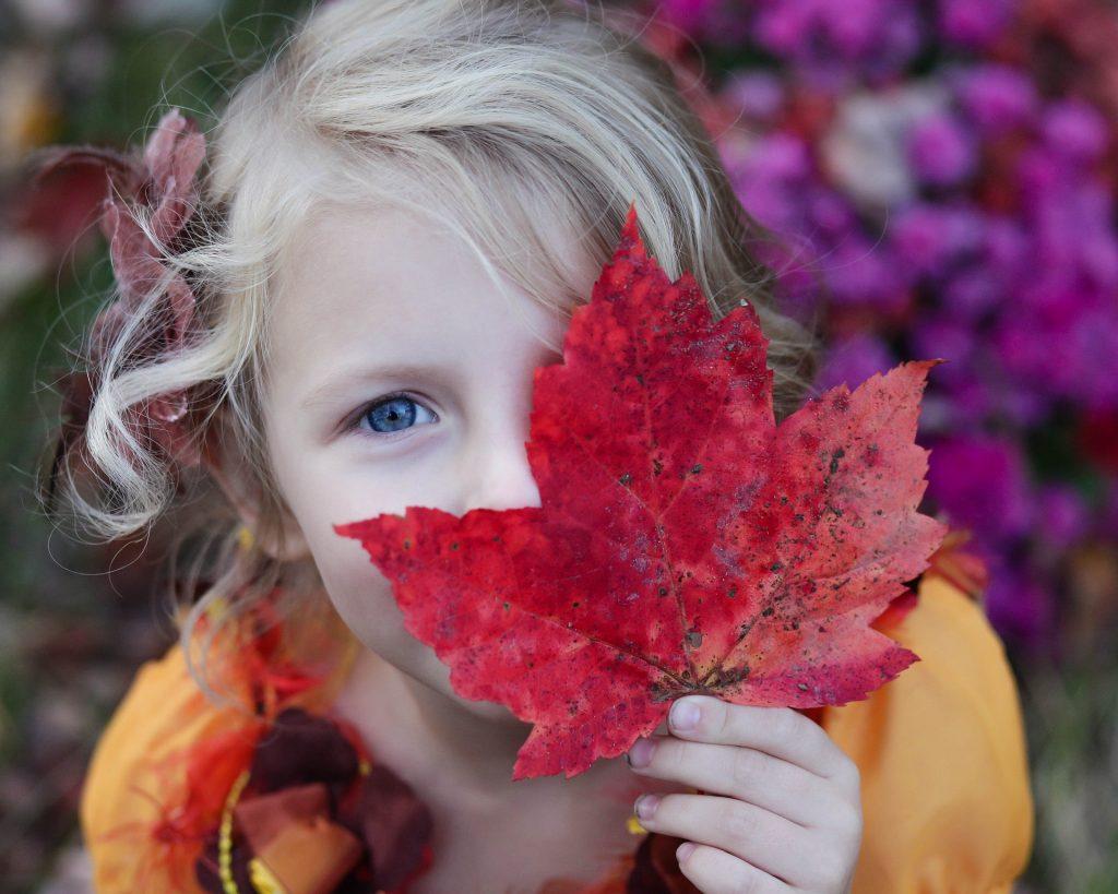 una bambina che si copre il viso con una foglia rossa lasciando scoperti i capelli lunghi e biondi e un occhio blu