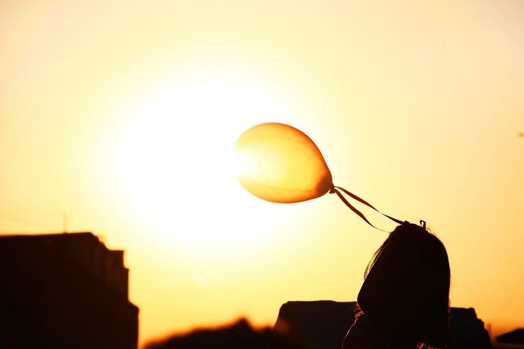 persona in ombra che al tramonto guarda un palloncino giallo in cielo