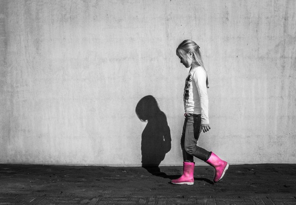 foto in bianco e nero, una bimba cammina a testa bassa accanto ad un muro che riflette la sua ombra, con stivaletti rosa