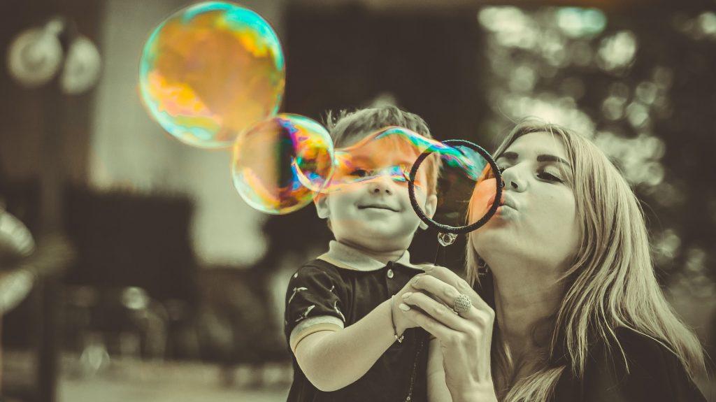 mamma con in braccio il figlio che fanno le bolle