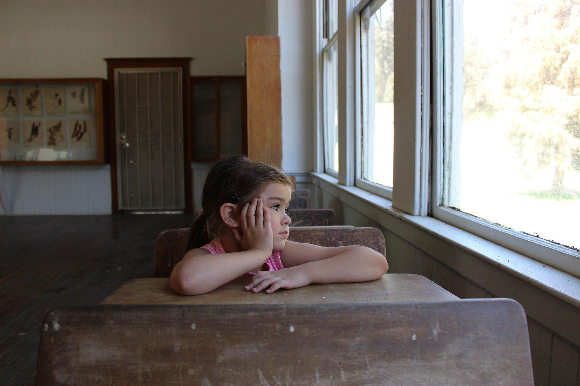 bambina sola in un banco di scuola guarda triste fuori dalla finestra