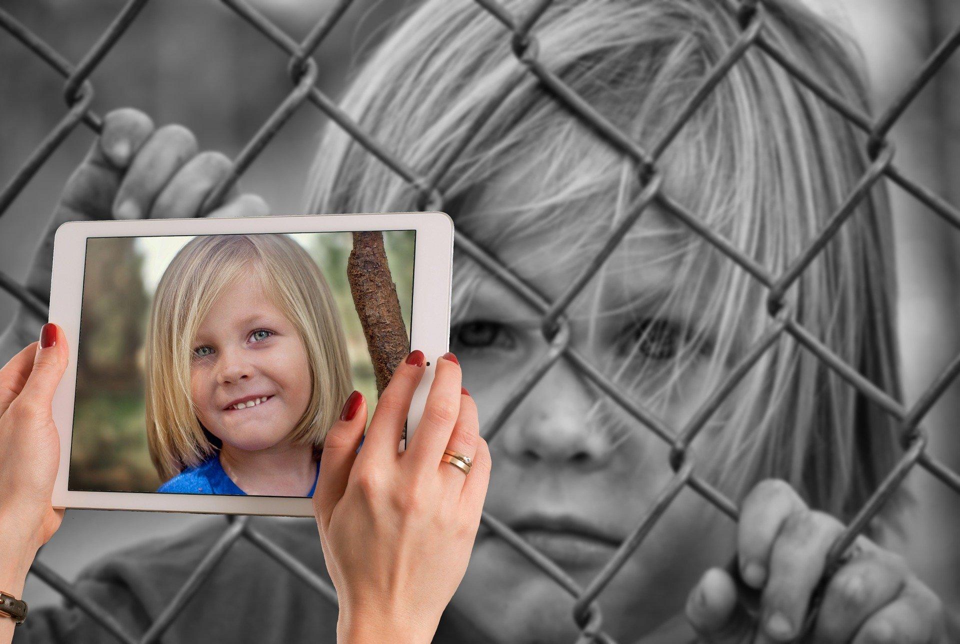 foto di una bambina che ride davanti alla bambina triste