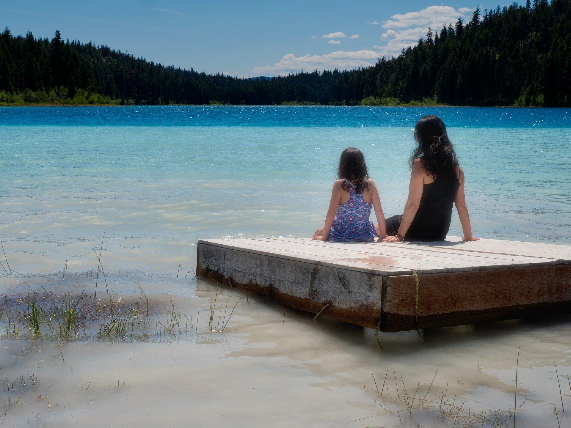 una donna e una bambina di spalle sedute davanti a un lago