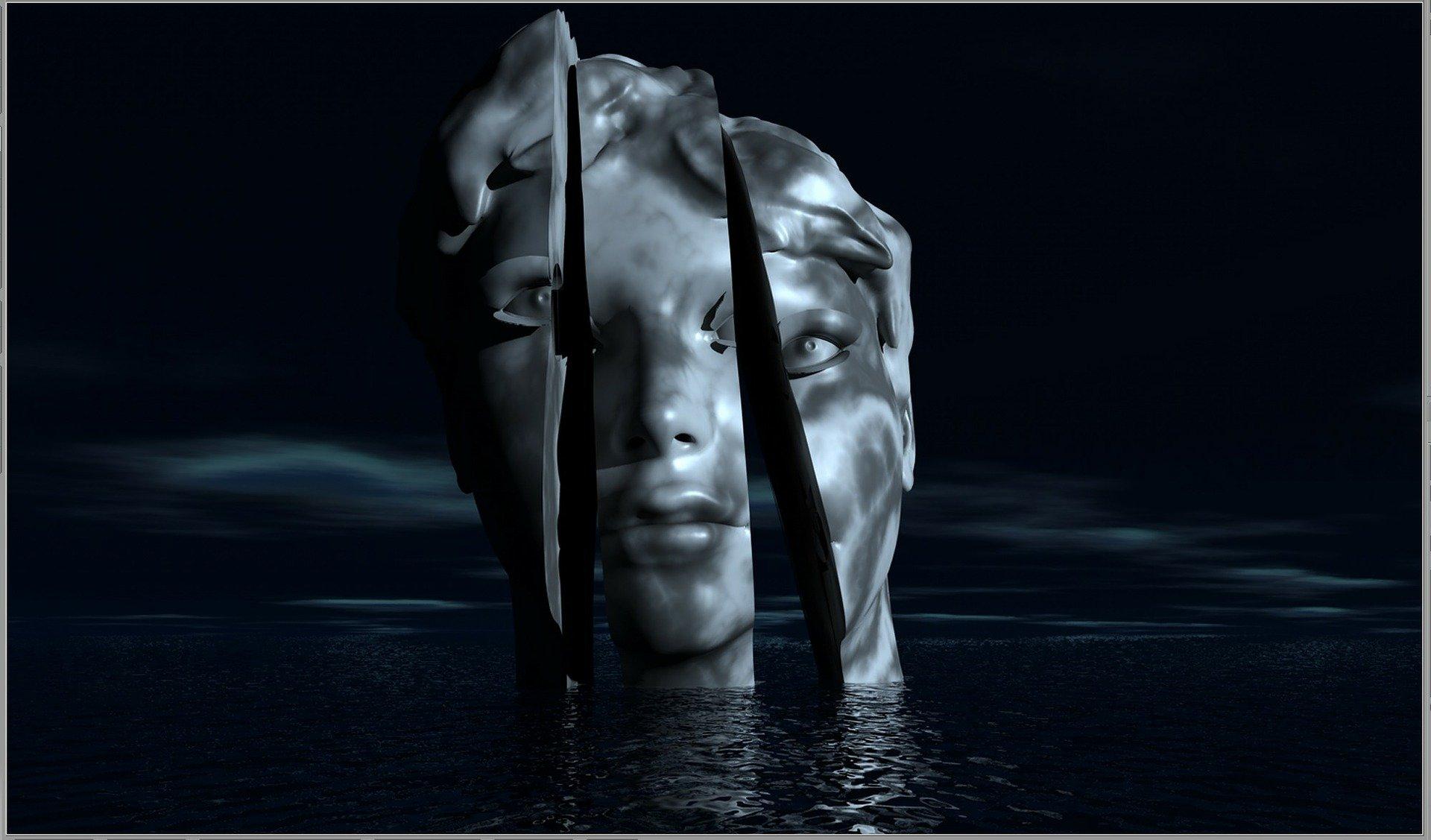 una testa in metallo tagliata in tre parti che affiora da un lago