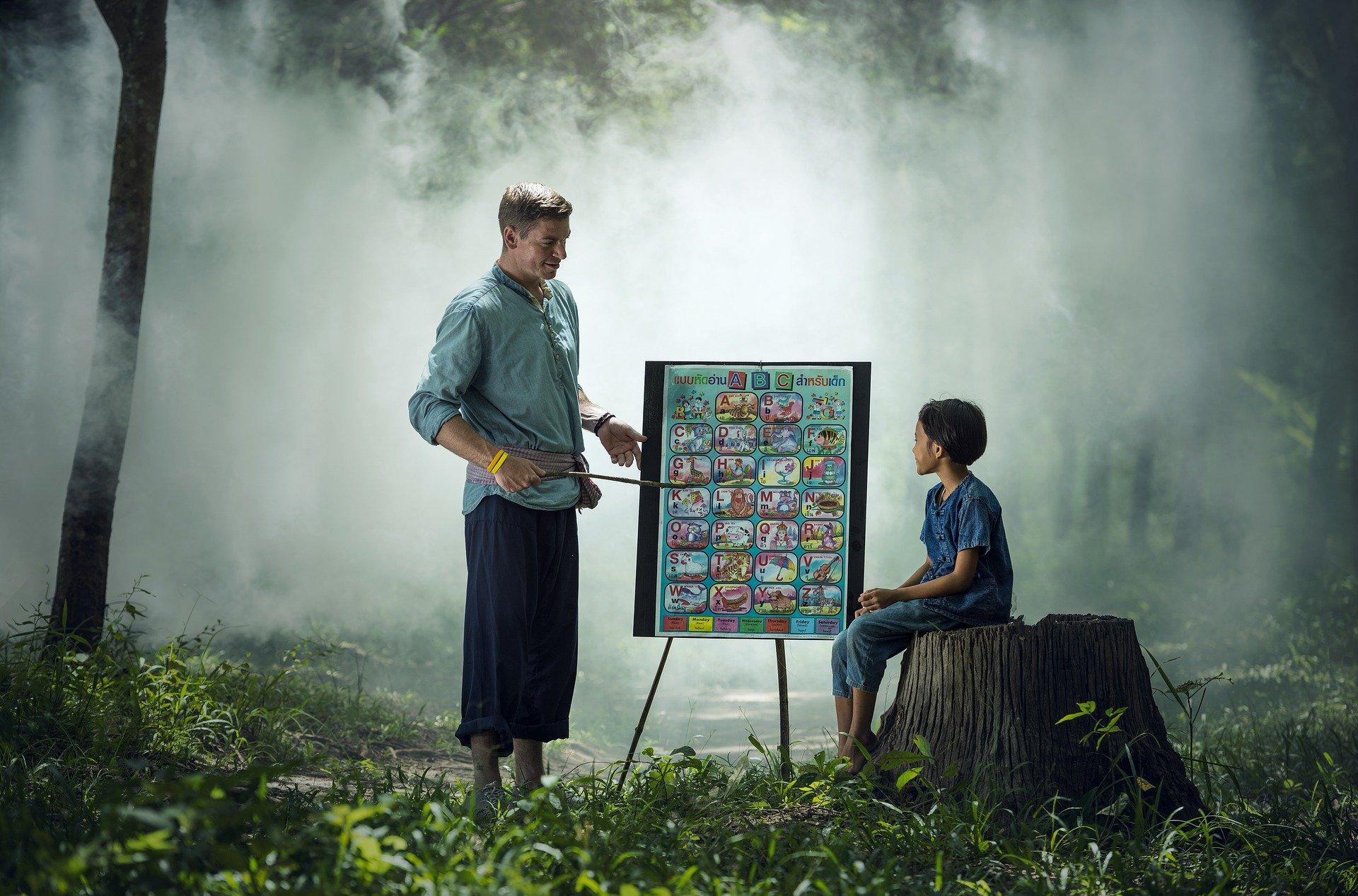 un insegnante in un bosco insegna l'alfabeto ad un ragazzo