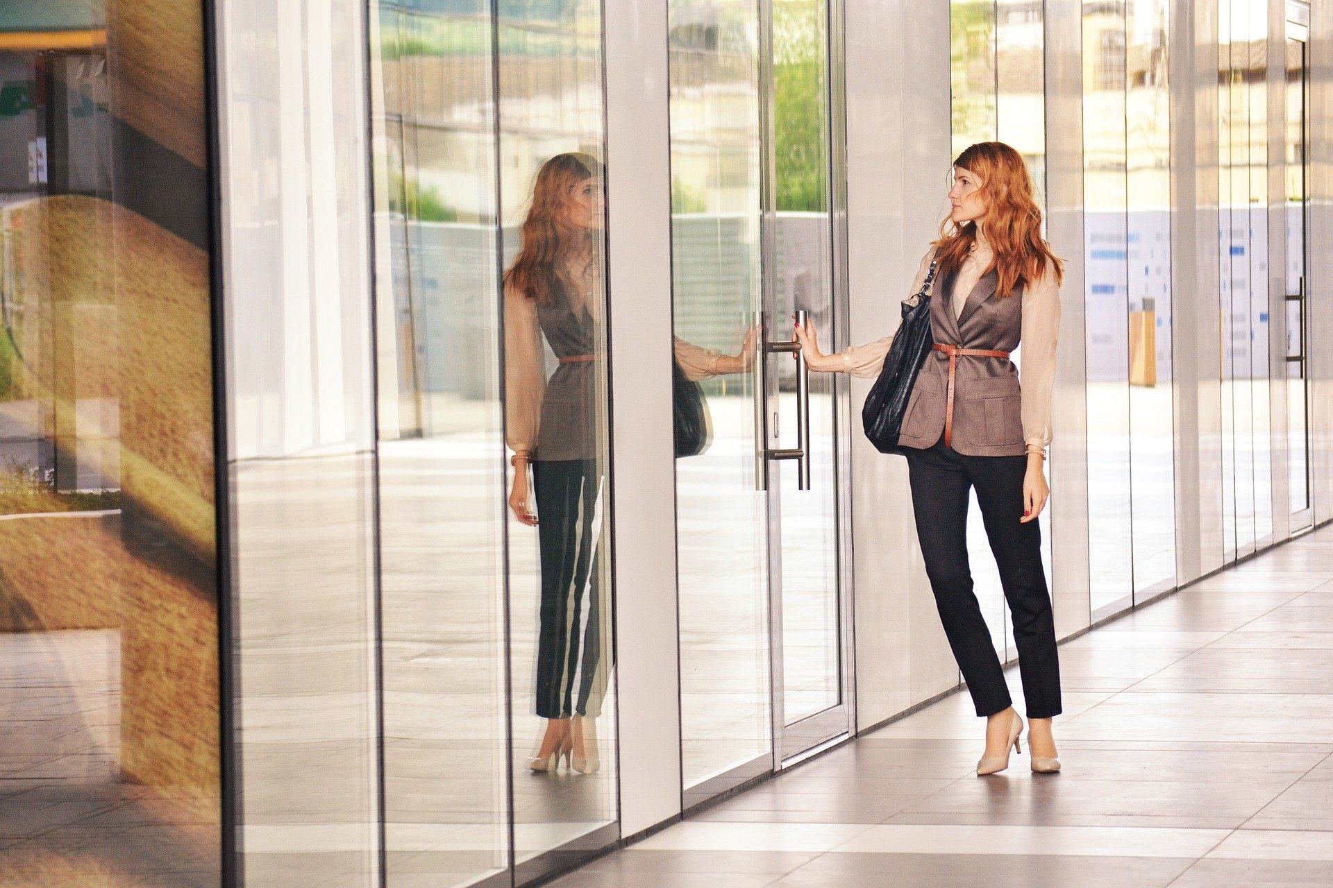 una donna che sta per entrare in una porta di un ufficio
