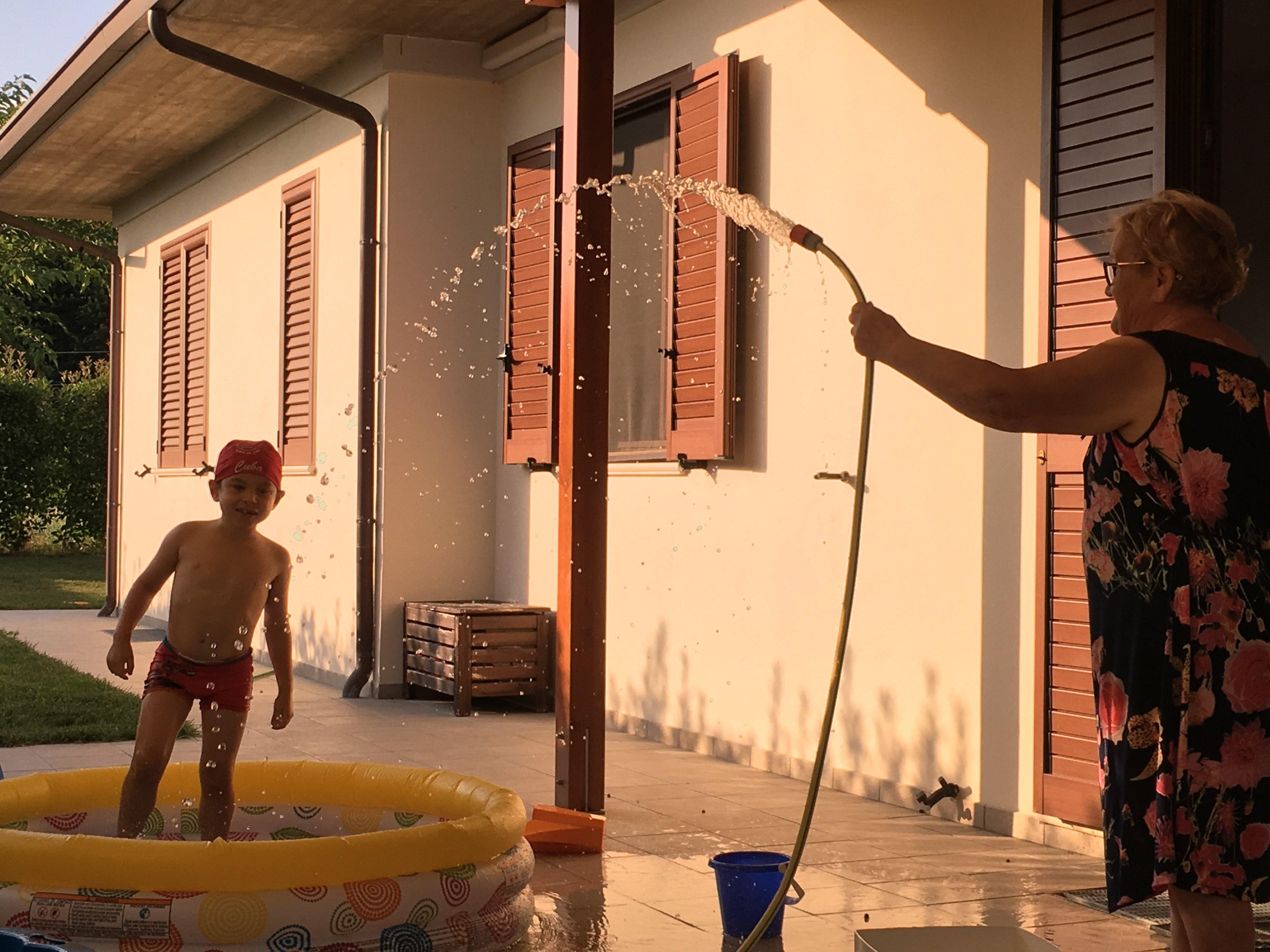 Maria tiene il tubo dell'acqua per far giocare Giuliano