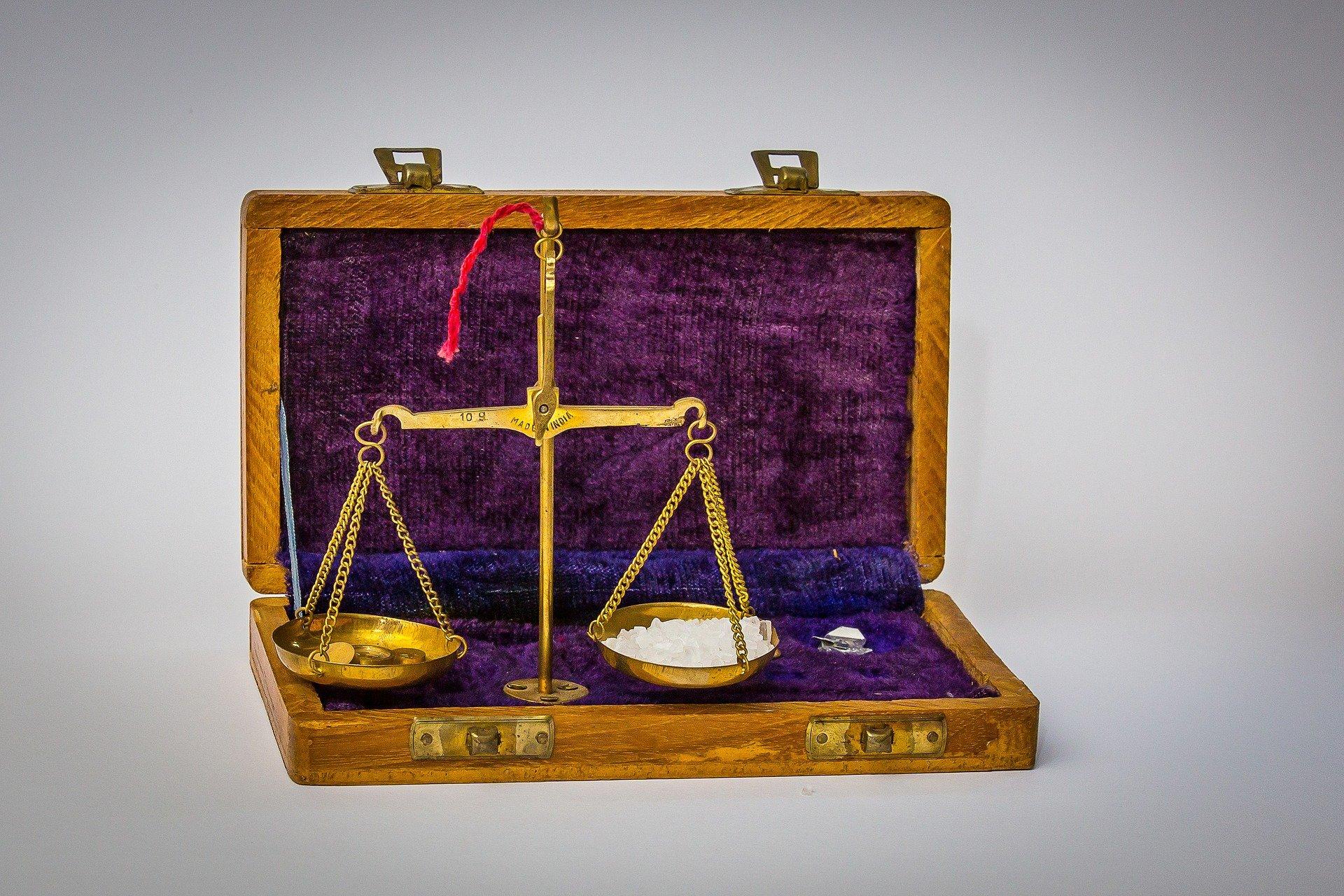 una valigia di velluto aperta con una bilancia orizzontale in equilibrio con materiali diversi