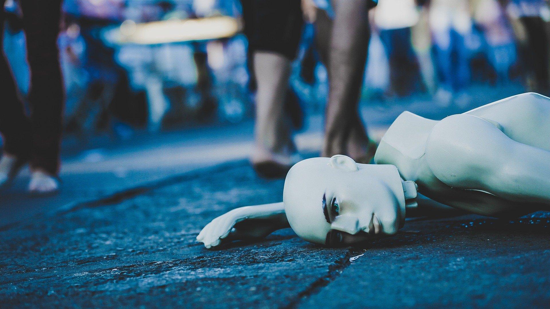 un manichino nudo a terra in mezzo alla gente