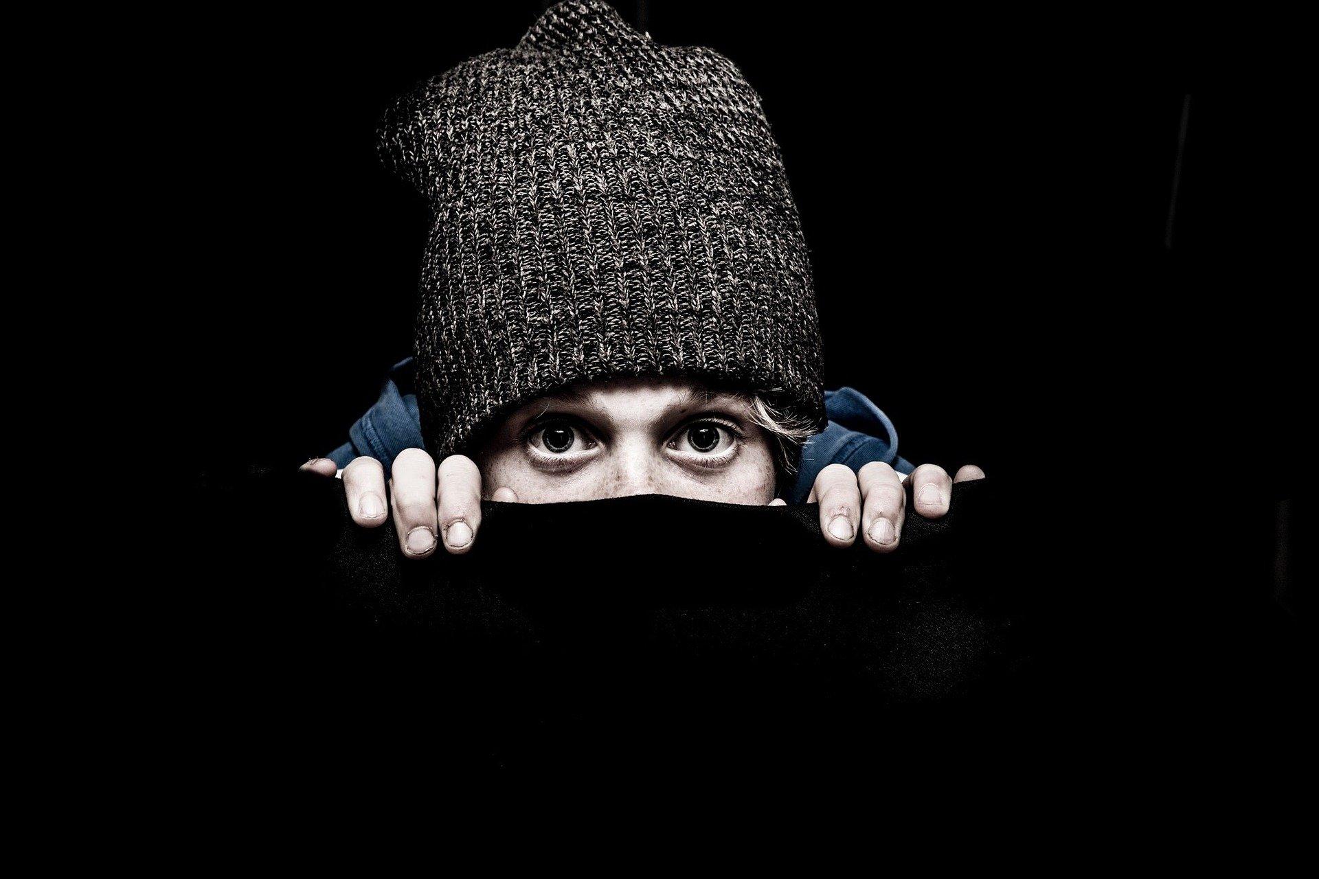 ragazzo dietro un muro nero che si nasconde e si vedono solo occhi e cappello