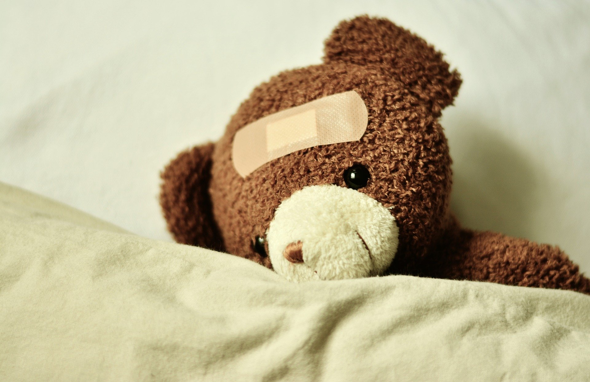 un orsacchiotto dentro il letto con un cerotto in testa