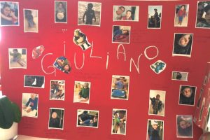 cartellone con appese foto di Giuliano e delle sue educatrici