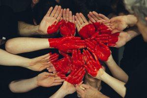 mani dipinte di rosso che tutte vicine disegnano un cuore