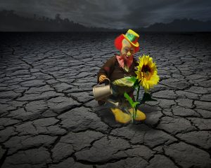 un clown annaffia un girasole che cresce al buio in una terra arida