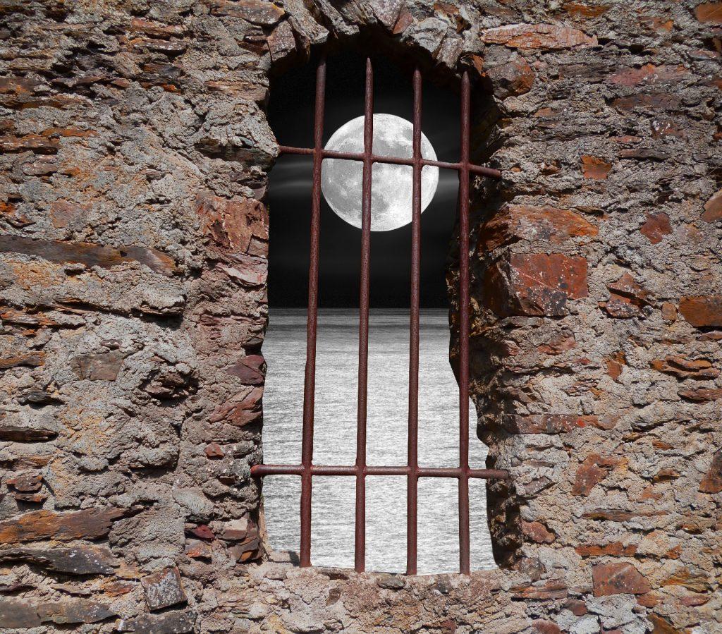muro in pietra con un'apertura sbarrata a ferro dalla quale si intravede la luna sul mare