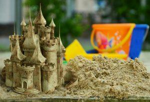 un castello elaborato di sabbia con secchiello e paletta sullo sfondo