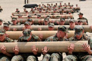 soldati che si allenano sollevando insieme dei tronchi