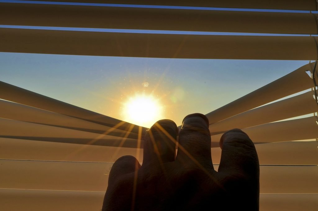 una mano schiude una veneziana dietro la quale appare il sole