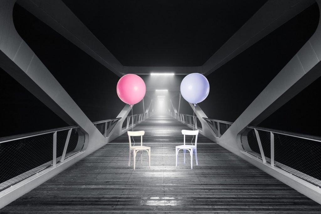 sopra un ponte due sedie con due palloncini uno blu uno rosa in immagine in bianco e nero