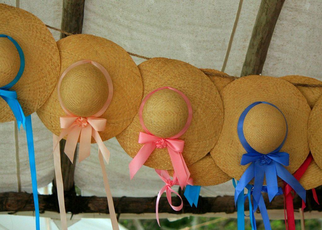 più cappelli femminili di paglia con fiocchi blu e rosa appesi