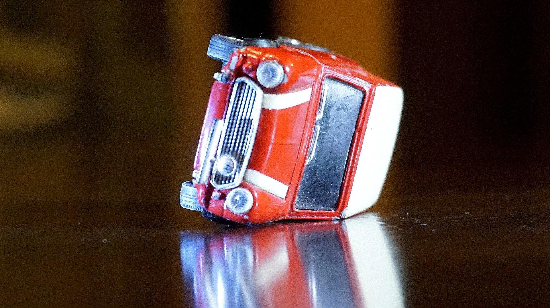 auto mini giocattolo rossa a strisce bianche rovesciata da un lato su un tavolo