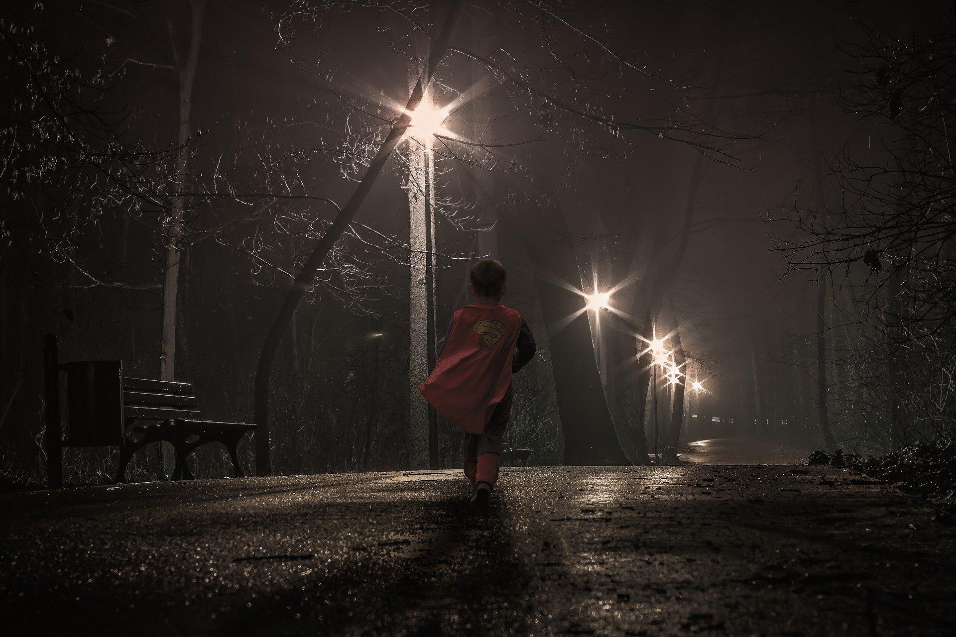un bambino travestito da superman solo di notte lungo una via
