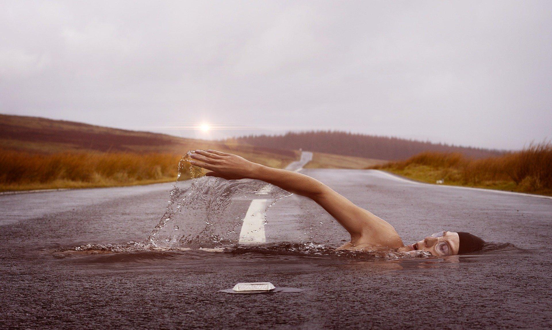 un uomo che attraversa una strada nuotando