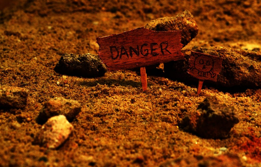 terra rossa con cartello di pericolo e cartello con teschio