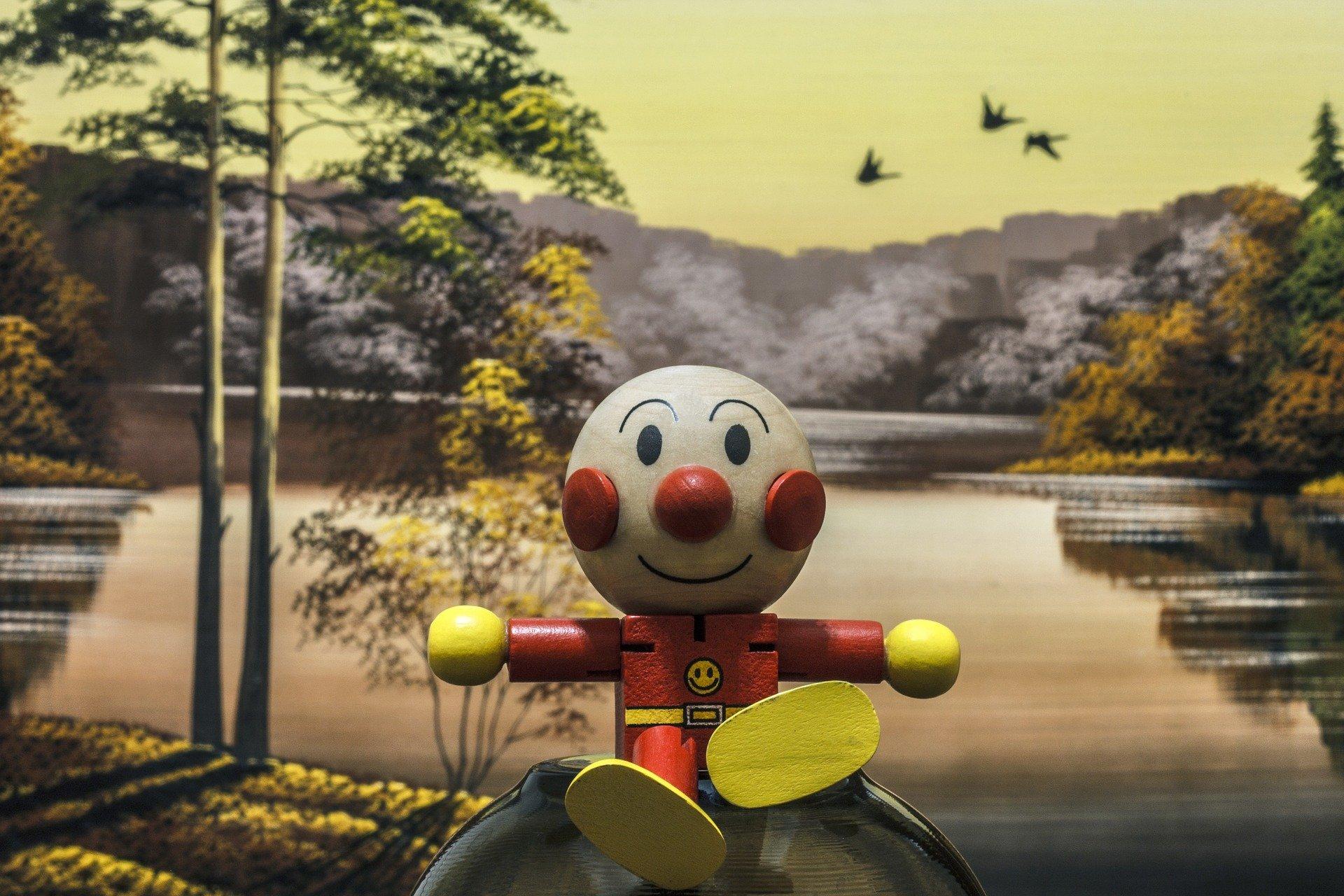 un bambino di legno e sullo sfondo un paesaggio con un lago