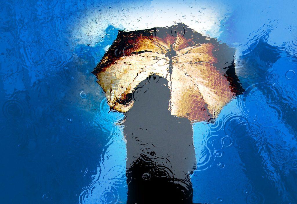 immagine di una donna sotto l'ombrello riflessa da una pozzanghera d'acqua sulla quale sta piovendo