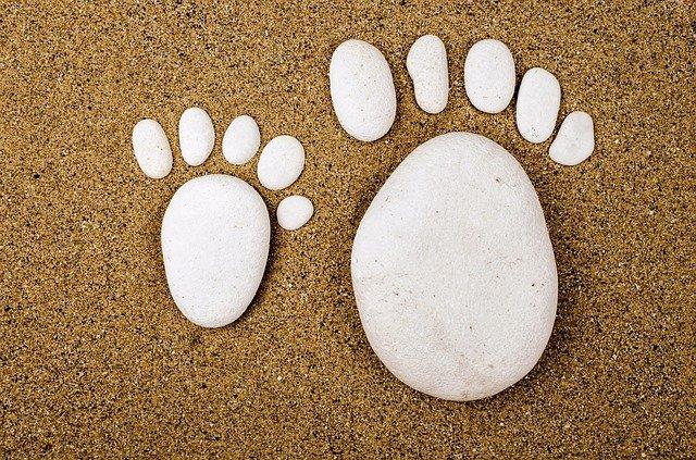 Dei sassi costruiscono due impronte di piedi adulto e bambino