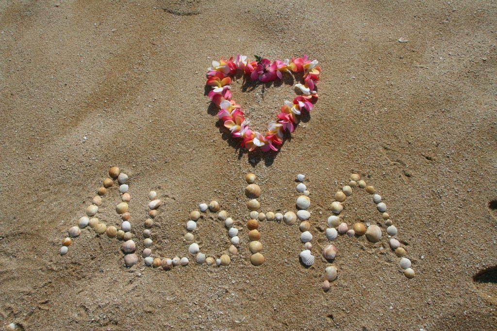 un cuore di fiori e la scritta aloha fatta con conchiglie sulla sabbia
