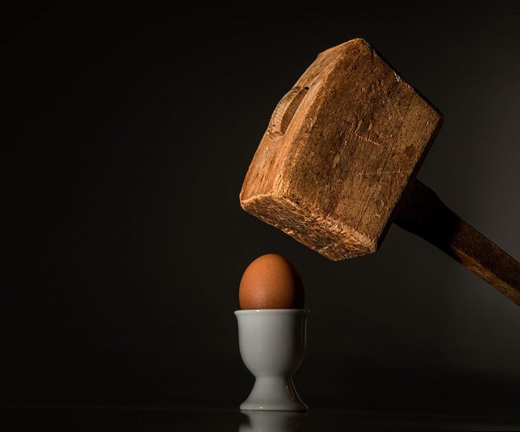 uovo che sta per essere schiacciato da un grande martello di legno