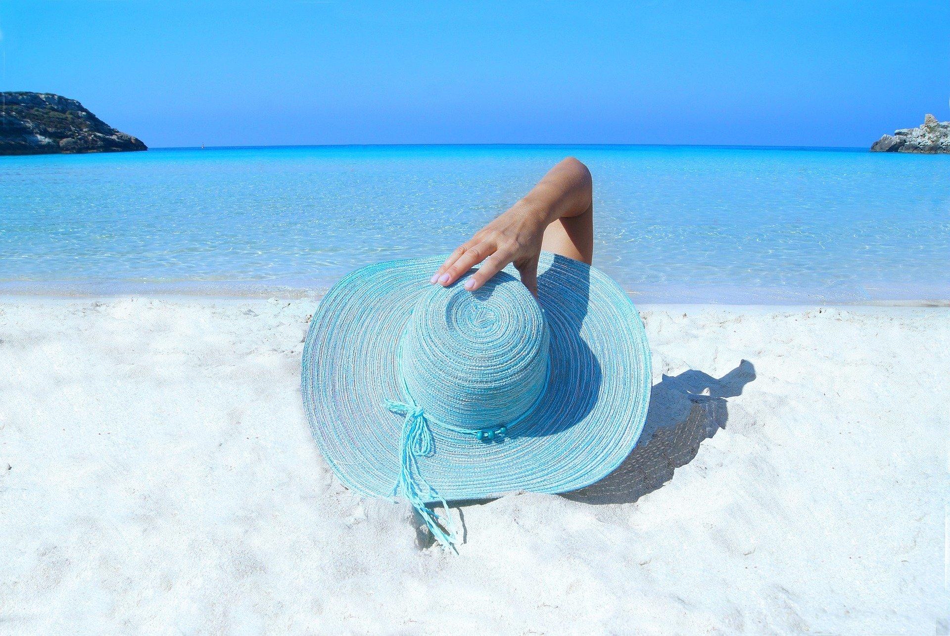 donna sdraiata al mare della quale si vede solo il cappello e il braccio