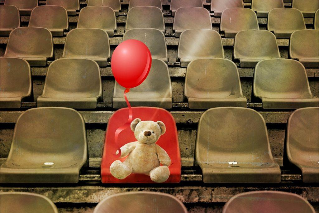 sedie di una tribuna vuote e marroni, solo una rossa occupata da un orsacchiotto che tiene in mano un palloncino rosso