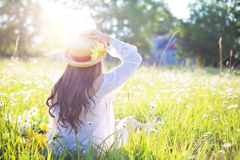 ragazza con capelli lunghi, cappello e camicetta bianca seduta in mezzo ad un prato di spalle
